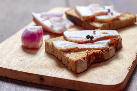 Lard with black bread and onions on a wooden board.