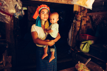 Long Neck Woman wearing at traditional costume is sitting with her child. Tribal village Northern Thailand.