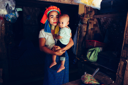 Long Neck Woman wearing at traditional costume is sitting with her child. Tribal village Northern Thailand. Stock Photo