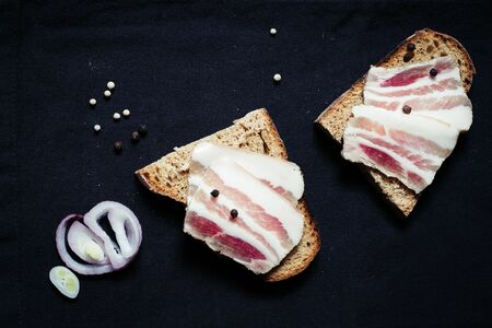 Lard with black bread and onions on a wooden board on a tablecloth Banco de Imagens