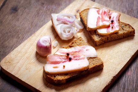 Lard sandwich with black bread and onions on a wooden board. Banco de Imagens