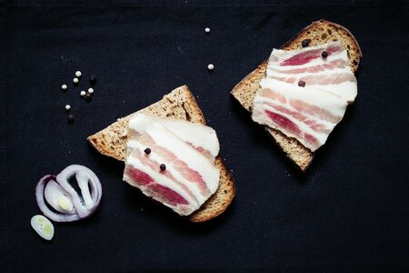 Sandwich with lard with black bread on the tablecloth on the wooden table 写真素材