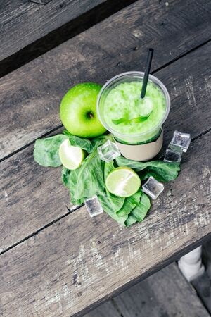 Green apple smoothie in glass and kale leaves on rustic wooden table. Summer Detox shake background