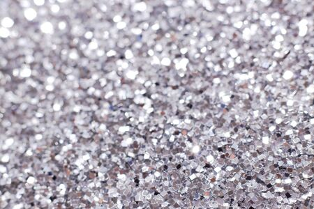 Silver glitter texture. Festive sparkling sequins background closeup. Brilliant shiny walpaper for the day of St. Valentine, New Year and Christmas Holidays.