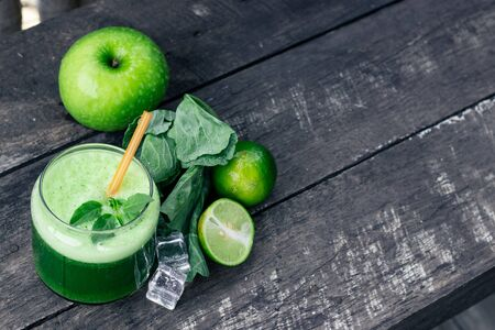 Green apple smoothie in glass and kale leaves on rustic wooden table. Stock fotó