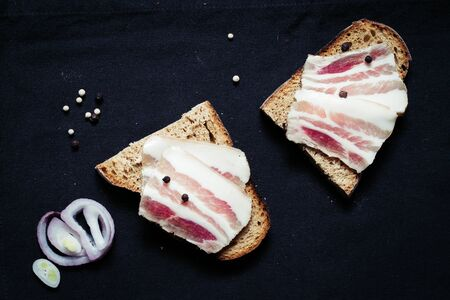 Sandwich with lard with black bread on the tablecloth on the wooden table Stock fotó