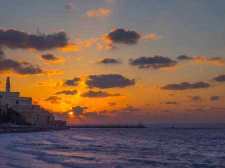 Coastal view of the ancient city of Yafo or Jaffanear Tel Aviv, Israel. Cityscape in sunset hour with clouds in the sky.