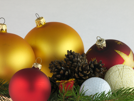 christmas golf: Red and gold Christmas balls on pine twig with a pine cones and golf ball.