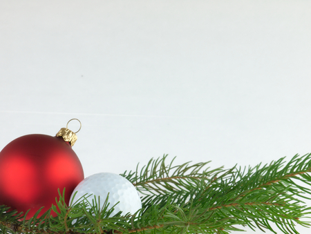 Red bauble Christmas Tree and golf ball with a sprig of pine trees on a chopping board and white background.