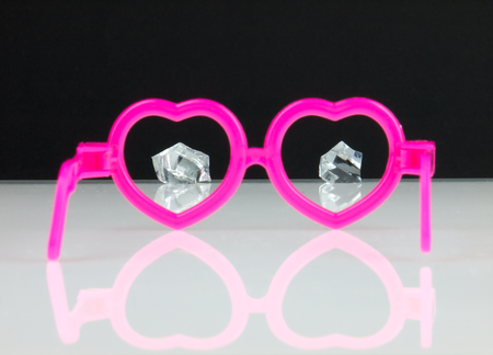 Pink glasses in the shape of hearts and diamonds visible in the distance. photo