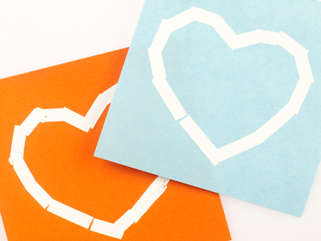 correction: Orange Sticky note with heart symbol drawn with the correction tape. Stock Photo