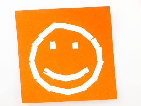 cara de alegria: Naranja Sticky nota con el s�mbolo de una cara feliz dibujada con la cinta correctora.