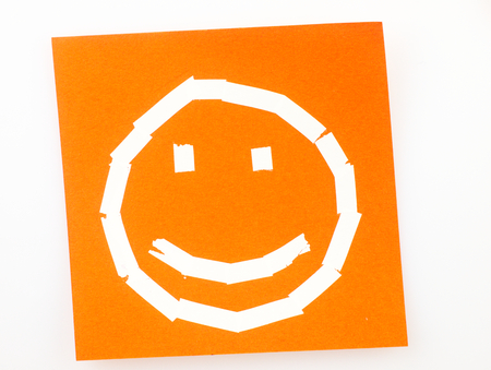 correction: Orange Sticky note with the symbol of a happy face drawn with the correction tape.
