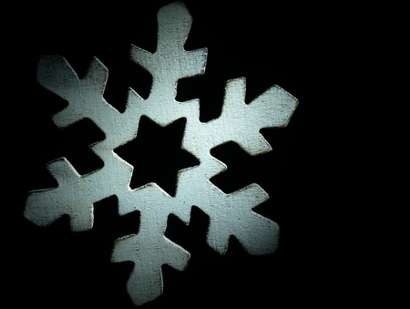 Huge white wooden snowflake and black background. photo
