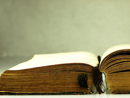 history background: Old, open book with a damaged cover. Stock Photo