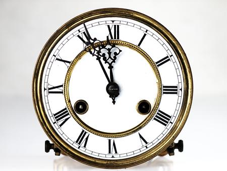 Mecanismo del viejo reloj. Cara de reloj y las manos que muestra cinco minutos para la medianoche.