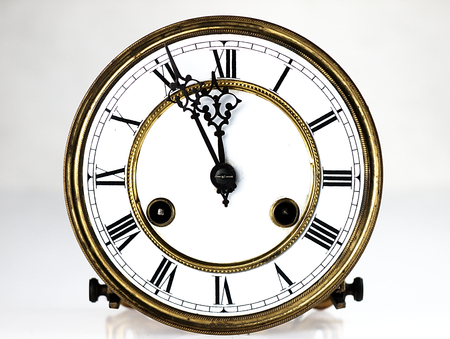 Mechanism of old clock. Clock face and hands showing five minutes to midnight.