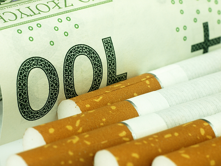 Smoking is expensive habit. Cigarettes on money background. photo