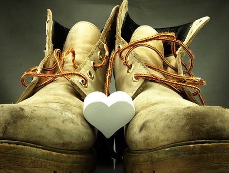 muddy clothes: Old pair of heavy military boots and white delicate heart between them.