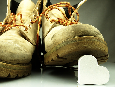 heavy heart: Old military boots, very heavy, trampling a delicate white heart.