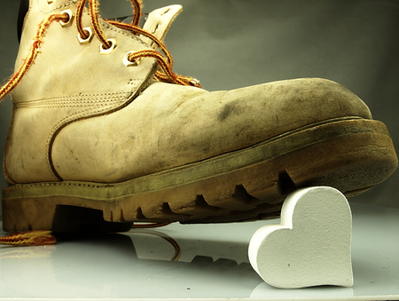 muddy clothes: Old military boots, very heavy trampling a delicate white heart. Stock Photo