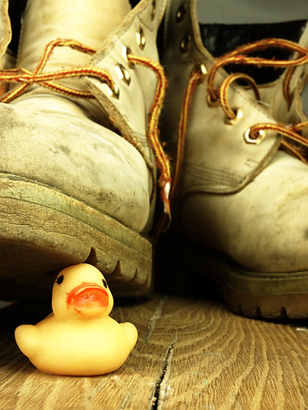 annexation: Yellow rubber under the old, dirty and heavy military boot. The view from the perspective of frogs. Stock Photo