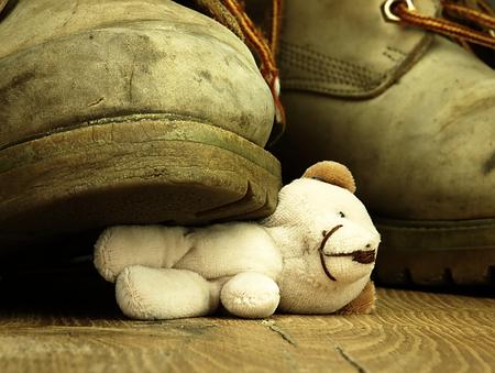 desprecio: Teddy bear bajo la vieja, sucia y pesada bota militar. La vista desde la perspectiva de las ranas.