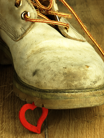 heart under: Red heart under the old, dirty and heavy military boot. The view from the perspective of frogs. Stock Photo