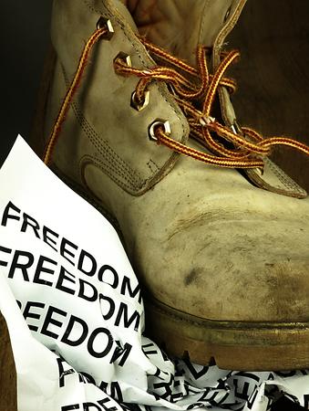 desprecio: Pedazo arrugado de papel con la palabra libertad bajo el viejo, sucio y pesado bota militar.