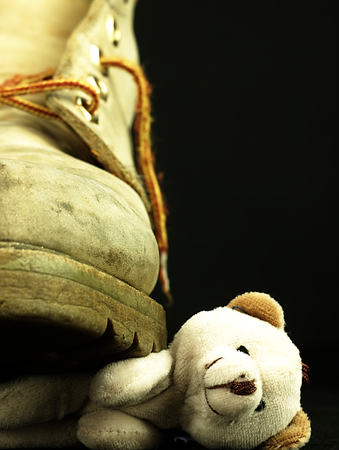 Teddy bear under the old, dirty and heavy military boot. The view from the perspective of frogs.
