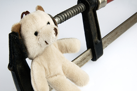 Carpenter clamp on the head teddy bear. The idea for the show stress and overload. Stock Photo