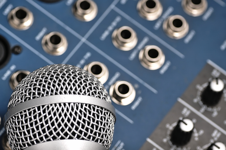 speaker system: Sound console with buttons in the background and a dynamic microphone in the foreground. Stock Photo