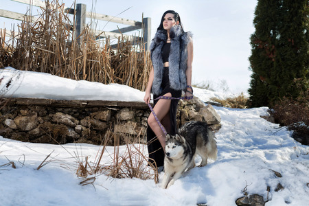 Elegant girl in a fur vest with the Laika dog photo