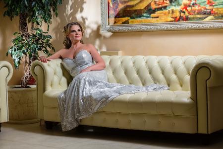 mujer elegante: Mujer elegante edad sentada en un sof� de cuero