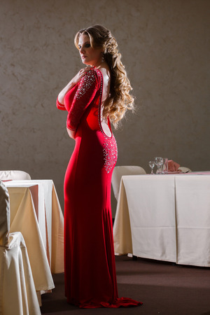 fitting in: Elegant woman aged in red dress fitting close