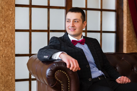 bridegroom: Bridegroom is sitting on a leather sofa and looking away Stock Photo