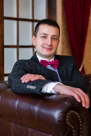 bridegroom: Portrait bridegroom sitting in a leather chair Stock Photo