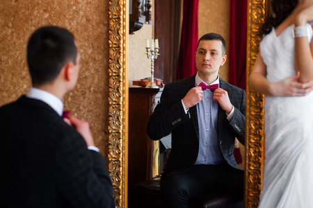 corrects: Bridegroom looks in the mirror and corrects butterfly
