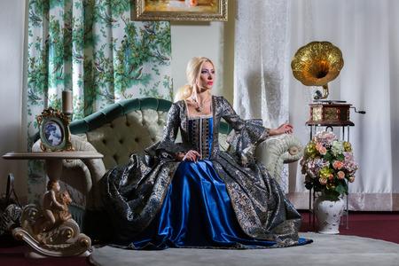 medieval dress: Mujer en alineada medieval se sienta en un sof�