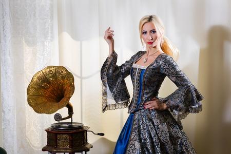 medieval dress: Muchacha en alineada medieval de pie junto a un gram�fono