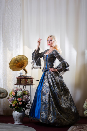 queen's theatre: Woman in medieval dress standing next to a gramophone
