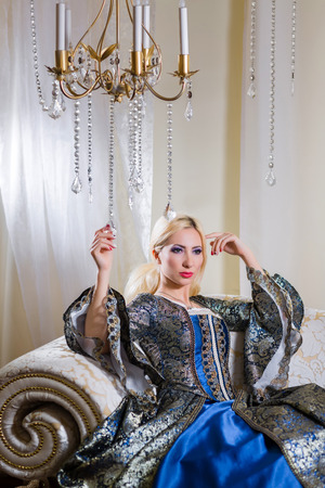 queen's theatre: Lady in medieval dress sits on a sofa under the chandelier Stock Photo