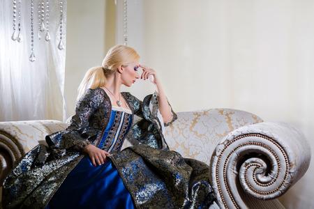 vestido medieval: Mujer en vestido medieval en el sof� pregunt�ndose Foto de archivo