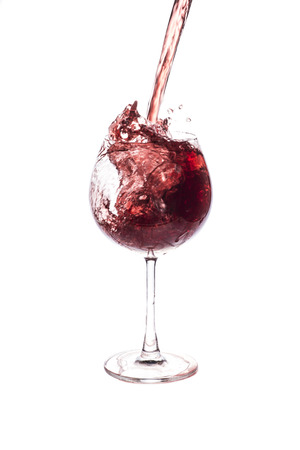 pouring red wine in to wine glass.
