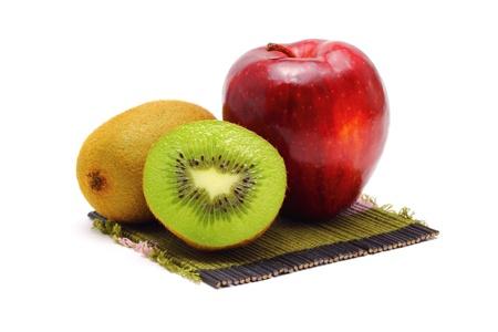 Apple and kiwi fresh fruit on bamboo mats white background