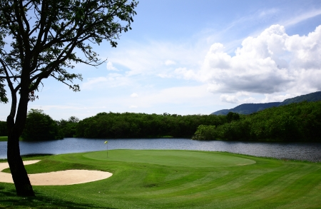 Golf course with gorgeous green and sand bunker photo