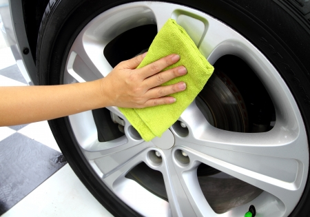 Hand with a microfiber wheel cleaning car wash