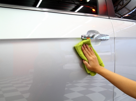 wash cloth: Hand with a microfiber wipe the car polishing Stock Photo