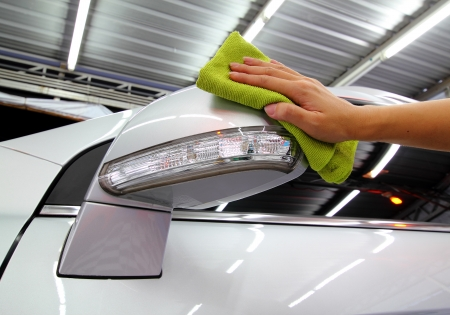 Hand with a microfible wipe the car side mirror polishing car wash