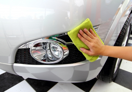 Hand with a microfible wipe the car polishing